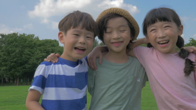 view of children with arms around smiling in summer at seoulforest (the third largest park in seoul city) - public park点の映像素材/bロール