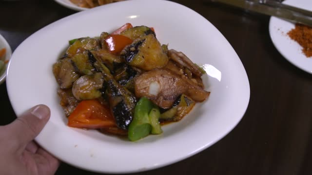 view of chinese food di san xian(fried potatoes, eggplant and peppers) being placed on the table - fried potato stock videos and b-roll footage
