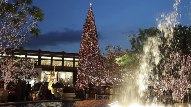 ms view of christmas tree in shopping center exterior framed by dramatic display of dancing water fountain with twilight blue sky / glendale, california - glendale california stock videos & royalty-free footage