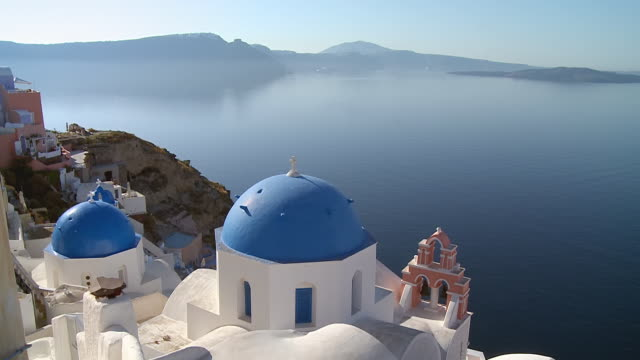 ws view of church at village oia with ocean / santorini, cyclades, greece - oia santorini stock videos & royalty-free footage