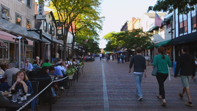 WS View of Church Street downtown with restaurants and tourists outdoors at cafe in Northern New England downtown at restaurant called Leunig's Bistro on brick streets / Burlington, Vermont, United States