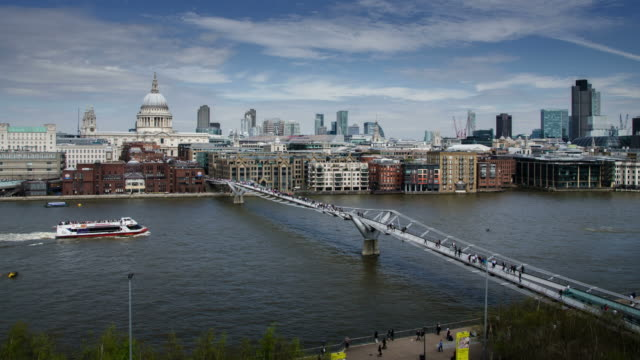 WS T/L View of City and St Pauls across River Thames Commuters cross Millennium Bridge with clouds / London, Greater London, United Kingdom