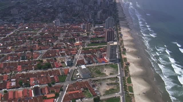 vídeos y material grabado en eventos de stock de ws aerial td view of city at praia grande coastline / sao paulo, brazil - praia