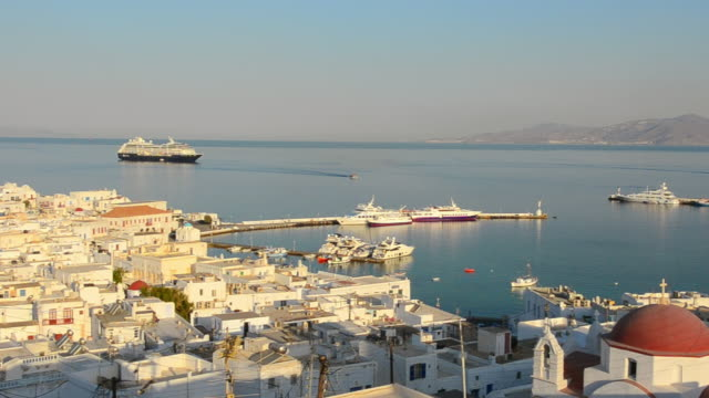 ws pan view of city at sunrise with white village port greek above / mykonos, greece - mykonos stock videos and b-roll footage