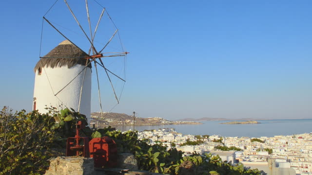 ws view of city at sunrise with white windmill above city white village port greek / mykonos, greece - mykonos stock videos and b-roll footage