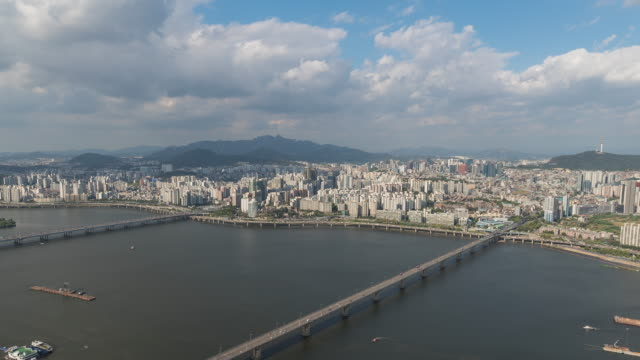 view of city buildings and n seoul tower (famous tourist destinations) by the han river and clouds moving in seoul - wäldchen stock-videos und b-roll-filmmaterial