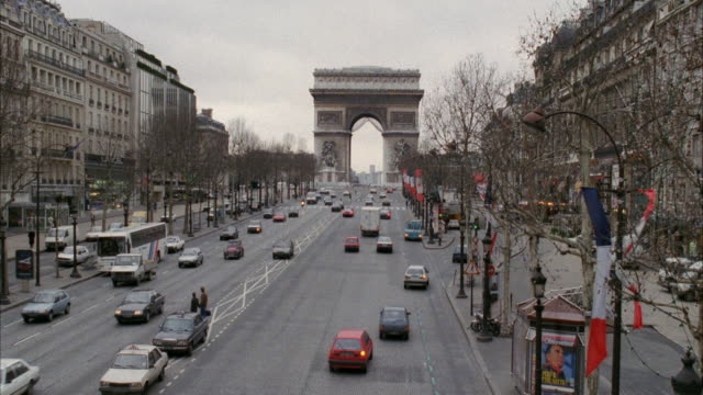 WS View of city cars travelling on road and other cars parking at road side / Paris, France
