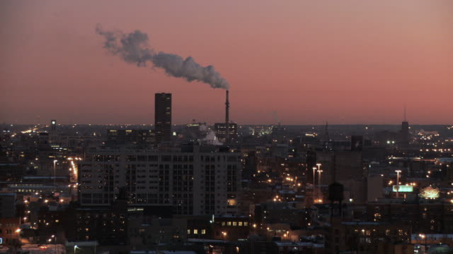 ws view of city factory emitting steam at dusk in winter / chicago, illinois, usa - 工場の煙突点の映像素材/bロール