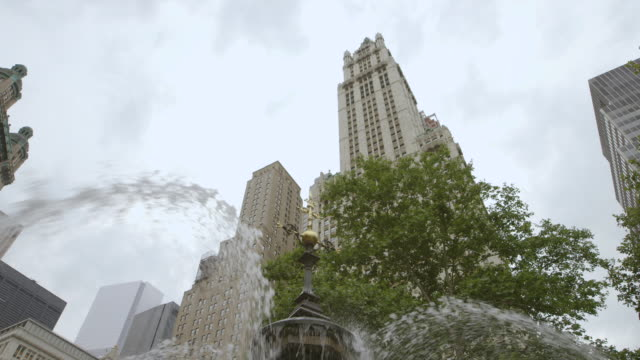 ms tu view of city hall park fountain in front of woolworth building / manhattan, new york city, new york state, united states - woolworth building stock videos & royalty-free footage