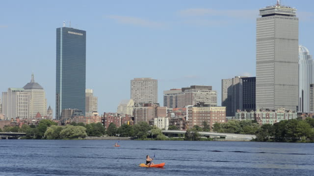 WS View of city located near river and people sculling boat on water / Boston, Massachusetts, United States