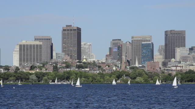 vídeos de stock e filmes b-roll de ws view of city located near river and sailling boats moving on river / boston, massachusetts, united states - remo com par de remos