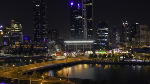 WS T/L TU View of city skyline and skyscrapers on bank of Yarra River at night / Melbourne, Victoria, Australia