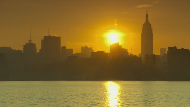 ws view of city skyline at sunrise with empire state building / new york city, new york, usa - 逆光点の映像素材/bロール