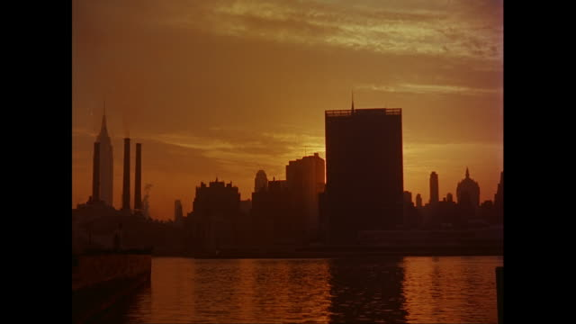 stockvideo's en b-roll-footage met ws view of city skyline with united nations headquarters and empire state building at sunset / new york city, new york state, united states - hoofdkantoor
