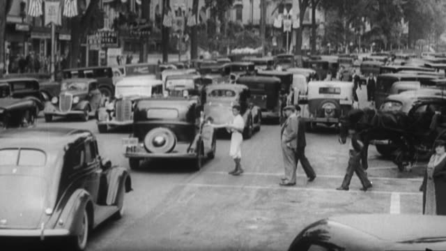 ms view of city street traffic / united states - 1930 stock-videos und b-roll-filmmaterial