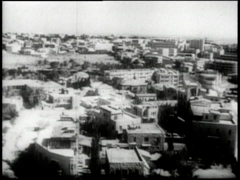 vídeos de stock e filmes b-roll de 1945 montage view of city through arched window / ha rooftops of city buildings / ls cars driving on city street / ha people walking in circular park / ls family shopping at outdoor market / palestine - palestino