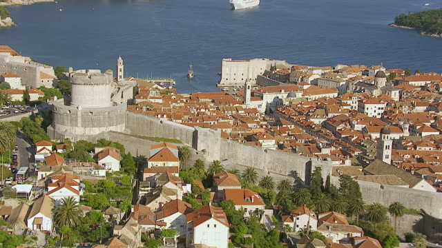 MS AERIAL ZO View of city wall and ship entering on to harbor / Dubrovnik, Dubrovnik Neretva County, Croatia