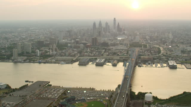 stockvideo's en b-roll-footage met ws aerial view of city with benjamin franklin bridge and delaware river and skyscraper on distance at sunset time / philadelphia - benjamin franklin bridge