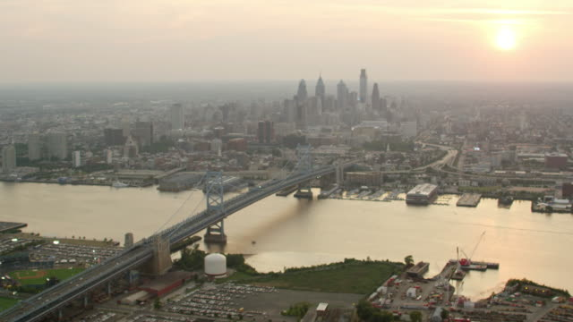 WS AERIAL View of city with benjamin franklin bridge and Delaware river at sunset time / Philadelphia