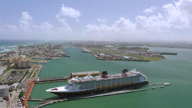 vídeos de stock e filmes b-roll de ws aerial pov view of city with cruise ship moored at sea / old san juan, san juan, puerto rico, united states - embarcação comercial