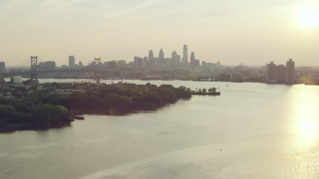 ms aerial view of city with delaware river and benjamin franklin bridge / philadelphia - デラウェア川点の映像素材/bロール