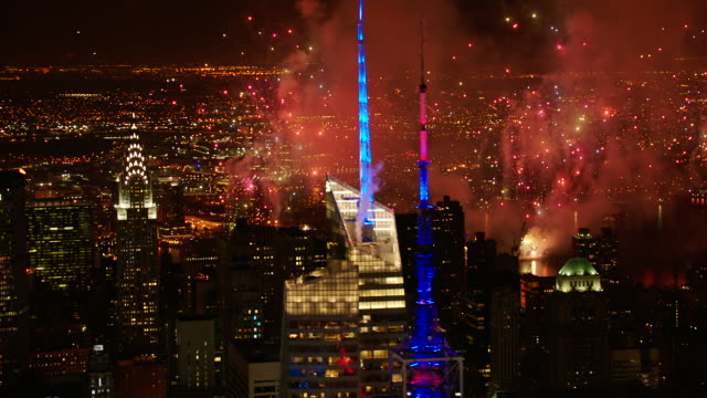 MS ZO AERIAL View of city with fireworks at hudson river and multi colored tower at night / New York City