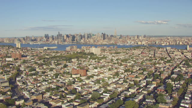 ws aerial view of city with hudson river and manhattan in in distance / jersey city, new jersey, united states - river hudson stock videos & royalty-free footage
