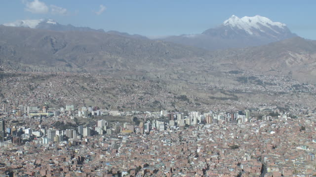 ws view of city with snowy mountain in background / la paz , bolivia - la paz region la paz stock-videos und b-roll-filmmaterial