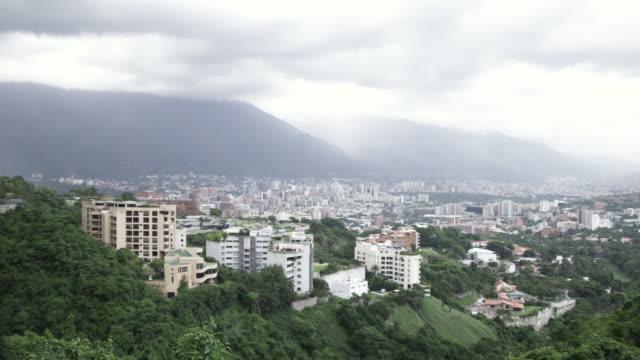 ws pan view of cityscape located near mountain / caracas, venezuela - caracas stock videos & royalty-free footage