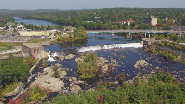 ws aerial pov view of cityscape with amoskeag mill yard dam / manchester, new hampshire, united states - new hampshire stock-videos und b-roll-filmmaterial