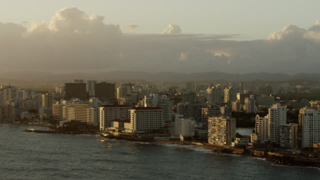 vidéos et rushes de ws aerial pov view of cityscape with beachfront resorts and hotels during sunrise / san juan, puerto rico, united states - antilles occidentales