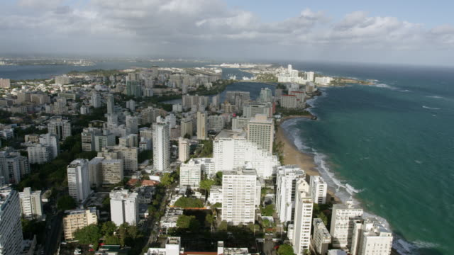 ws aerial pov view of cityscape with hotels and modern buildings, surf of parque beach / old san juan, san juan, puerto rico, united states - puerto rico stock videos and b-roll footage