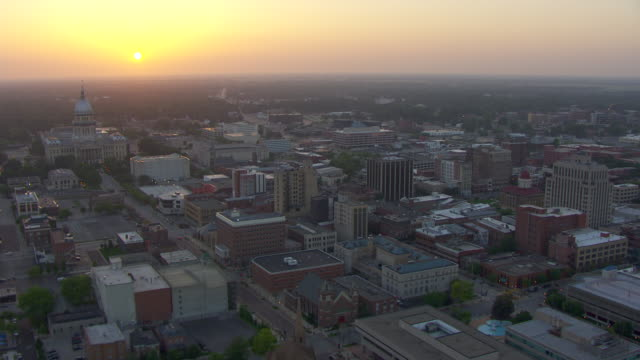 WS PAN AERIAL POV View of cityscape with Illinois State Capitol building at sunset / Springfield, Illinois, United States