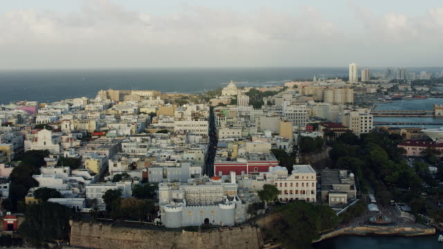 vídeos de stock, filmes e b-roll de ws aerial pov view of cityscape with la fortaleza in foreground / old san juan, san juan, puerto rico, united states - porto riquenho