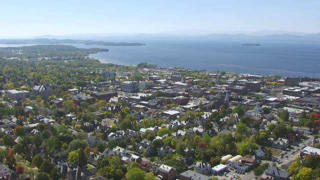 WS AERIAL POV View of cityscape with Lake Champlain in background / Burlington, Vermont, United States