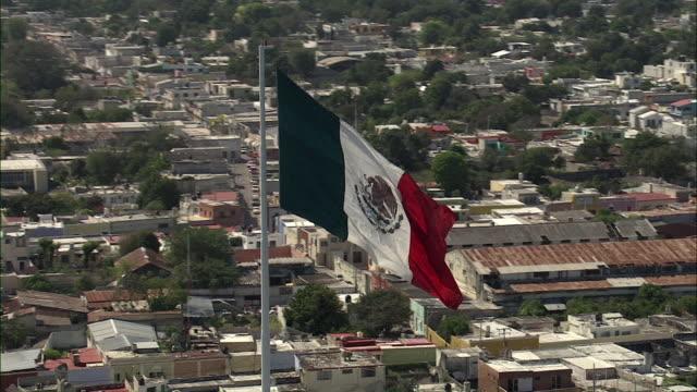WS POV View of cityscape with Mexican flag / Merida, Yucatan, Mexico