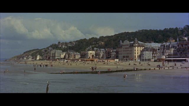 ws view of clam diggers at beach / deauvile, france - ノルマンディー点の映像素材/bロール
