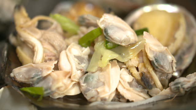 view of clam meat being gathered on pen shell - clam seafood stock videos and b-roll footage