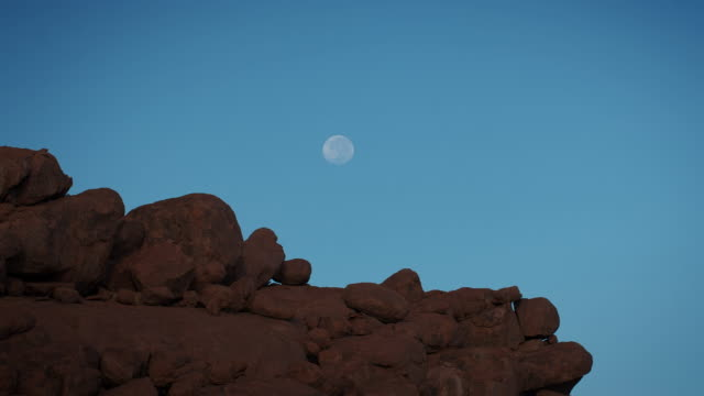ws t/l view of clear blue sky ghostly moon sinks down behind earth red rocks as sun lights them up from in front / spitzkoppe, windhoek, namibia - 巨礫点の映像素材/bロール