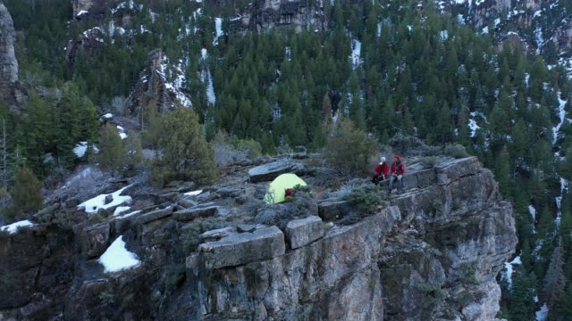 view of cliff with couple camping on top of it from aerial view - american fork canyon点の映像素材/bロール