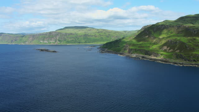 vídeos de stock e filmes b-roll de ws aerial view of cliffs on south coast near carsaig in hebrides on west coast with idyllic house location by shore and passing low over some small islands / isle or island of mull, argyll and bute, scotland - ilha mull