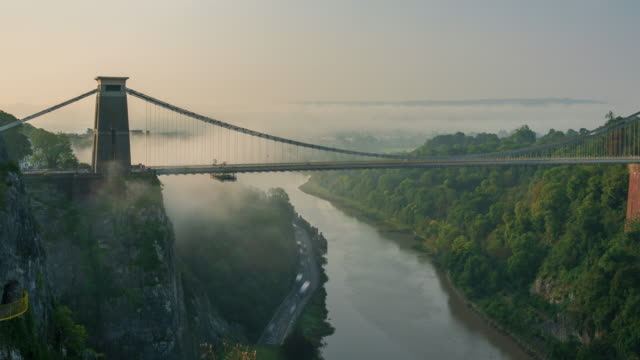 view of clifton suspension bridge in bristol, south west england with morning fog, 4k time-lapse (zoom-out) - somerset england stock videos & royalty-free footage