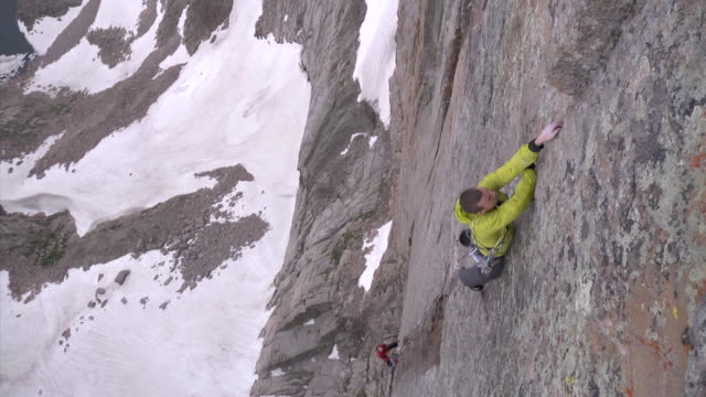 ws view of climber climbing big rock face with snow and lake below / estes park, colorado, united states - 崖点の映像素材/bロール