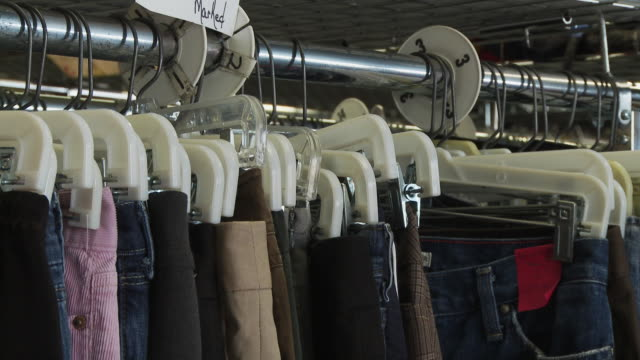 cu tu view of clothing racks in thrift store / morris, illinois, usa - kleidungsstück stock-videos und b-roll-filmmaterial