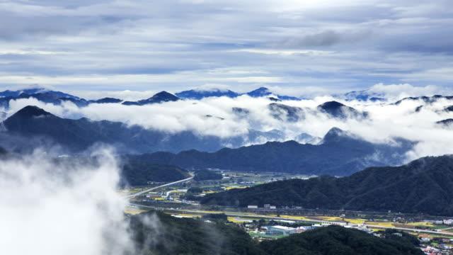 view of cloud sea ove mountain range and small village in pyeongchanggun, gangwon province - ローカルな名所点の映像素材/bロール