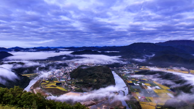 View of cloud sea over mountain range and small village in Pyeongchanggun, Gangwon Province