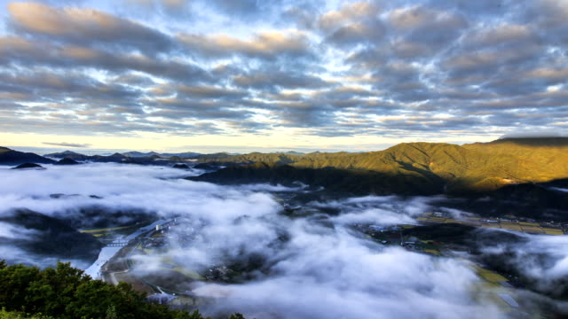 view of cloud sea over mountain range and small village in pyeongchanggun, gangwon province - wäldchen stock-videos und b-roll-filmmaterial