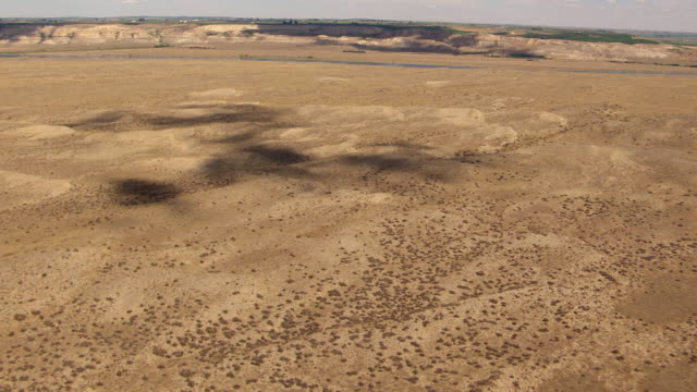 ws aerial view of cloud shadows on sand dunes in high desert near hanford site / richland, washington, united states - hanford nuclear reservation video stock e b–roll