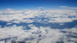 View of clouds and blue sky through airplane window