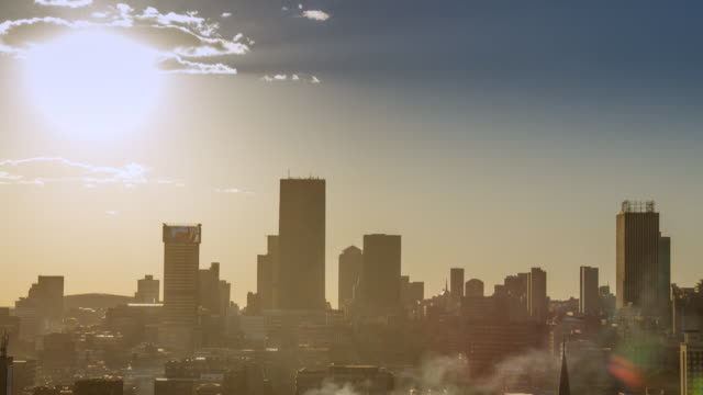 vídeos de stock e filmes b-roll de ws t/l view of clouds and steam across a silhouetted cityscape / johannesburg, gauteng, south africa - joanesburgo
